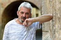 Portrait of a mature man looking at camera in urban background. Senior male with white hair and beard wearing casual clothes.
