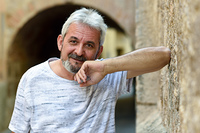 Portrait of a mature man looking at camera in urban background. Senior male with white hair and beard smiling wearing casual clothes.