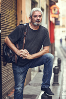 Portrait of a senior tourist man in urban background. Mature male with white hair and beard wearing casual clothes and travel backpack