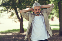 Portrait of a mature man, model of fashion, in an urban park. Senior male with white hair and beard wearing casual clothes.