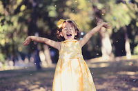 Portrait of a little girl running and playing in the park wearing a beautiful dress