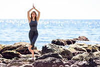 Young woman doing yoga in the beach. Female wearing sport clothes in eagle asana with defocused sea background.