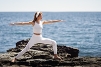 Young woman doing yoga in the beach. Female wearing white sport clothes in warrior 2 figure with defocused sea background.