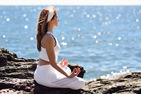 Young woman doing yoga in the beach. Female wearing white sport clothes in lotus figure with defocused sea background.