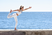 Young woman doing yoga in the beach. Female wearing white sport clothes with defocused sea background.