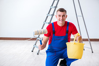 Male painter preparing for painting job at construction site