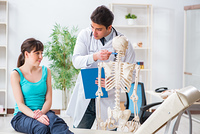 Doctor showing type of injury on skeleton to patient
