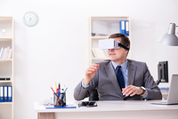 Businessman with virtual reality glasses in office