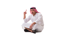 Young arab man sitting isolated on white