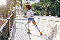 Young black woman on roller skates riding near the beach. Girl with afro hairstyle rollerblading on sunny promenade with sun backlight.