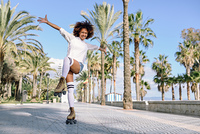Smiling black woman on roller skates riding outdoors on beach promenade with palm trees. Smiling girl with afro hairstyle rollerblading on sunny day.