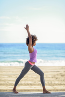 Black woman, afro hairstyle, doing yoga in warrior asana in the beach. Young Female wearing sport clothes with sea at the background