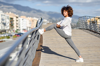 Young black woman doing stretching after running outdoors. Girl exercising with city scape at the background. Afro hair.