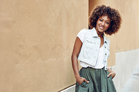 Young black woman, afro hairstyle, smiling near a wall in the street. Girl wearing casual clothes in urban background.