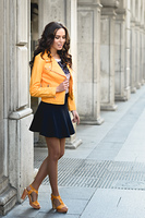 Young brunette woman, model of fashion, wearing orange modern jacket and blue skirt. Pretty caucasian girl with long wavy hairstyle. Female in urban background.