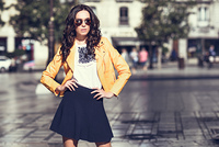 Young brunette woman with sunglasses. Girl, model of fashion, wearing orange modern jacket and blue skirt, standing in urban background.