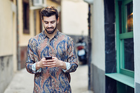 Young smiling man wearing casual clothes looking at his smartphone in the street. Guy with beard and modern hairstyle in urban background