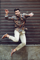 Young bearded man jumping in urban background with open arms wearing casual clothes. Guy with beard and modern hairstyle in the street.
