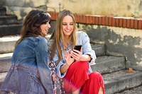 Two happy women sharing social media with smart phone outdoors sitting on urban steps. Friends girls.