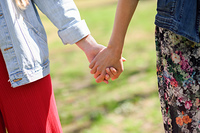 Two young women in walking holding her hands in urban park. Lifestyle concept. Front view.