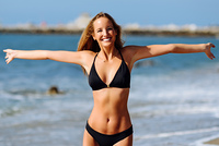 Young blonde woman with beautiful body in swimwear on a tropical beach with open arms. Caucasian female with straight long hairstyle wearing black bikini.