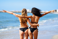 Rear view of two young women with beautiful bodies in bikini having fun on a tropical beach. Girls with open arms.