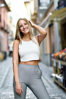 Young woman smiling in urban background. Blond girl with straight hairstyle wearing casual clothes in the street.