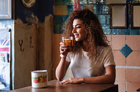 Young arabic woman with thoughtful gesture sitting in a beautiful bar with vintage decoration. Arab girl in casual clothes drinking a soda.