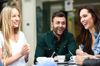 Multiracial group of friends having a coffee together. Two women and a man at cafe, talking, laughing and enjoying their time. Lifestyle and friendship concepts with real people models