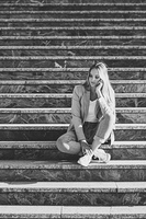 Thoughtful young caucasian woman in urban background. Blond girl wearing casual clothes in the street. Female with elegant jacket and blue jeans sitting on stairs.
