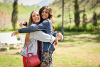 Two happy girls hugging in urban park. Blonde and brunette girls wearing casual clothes outdoors.
