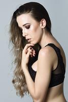 Woman with long hair wearing black lingerie. Beautiful caucasian woman with very long hair. Female wearing black lingerie. Wavy hairstyle. Studio shot.