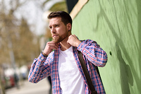 Attractive young man standing in urban background. Lifestyle con. Attractive young man standing in urban background. Guy wearing casual clothes. Lifestyle concept.