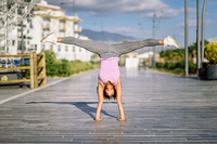 Black fit woman doing fitness acrobatics in urban background. Black fit woman doing fitness acrobatics in urban background. Young female exercising and working out hard.