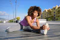 Young black woman doing stretching after running outdoors. Young black woman doing stretching after running outdoors. Girl exercising with city scape at the background. Afro hair.
