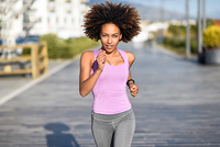 Black woman, afro hairstyle, running outdoors in urban road. . Black woman, afro hairstyle, running outdoors in urban road. Young female exercising in sport clothes.