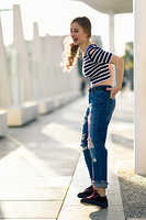 Funny blonde woman laughing in urban background. . Funny blonde woman laughing in urban background. Beautiful young girl wearing striped t-shirt and blue jeans in the street. Pretty russian female with pigtail.