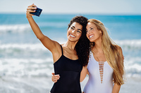 Two women taking selfie photograph with smartphone in the beach. Two young women taking selfie photograph with smart phone in swimsuits on a tropical beach.