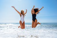 Two funny girls in swimsuit jumping on a tropical beach. Two funny girls with beautiful bodies in swimwear jumping on a tropical beach. Funny caucasian and arabic females wearing black and white swimsuits.