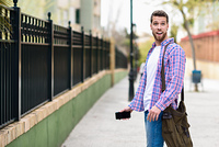 Young bearded man surprised in urban background. Lifestyle conce. Young bearded man surprised in urban background. Tourist wearing casual clothes. Lifestyle concept.