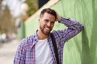 Attractive young man laughing outdoors. Lifestyle concept.. Attractive young man laughing outdoors. Funny guy wearing casual clothes in urban background. Lifestyle concept.