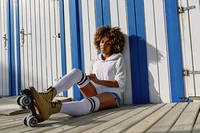 Young black woman on roller skates sitting near a beach hut. Girl with afro hairstyle rollerblading on sunny promenade.. Young black woman on roller skates sitting near a beach hut.