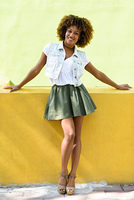 Young black woman, afro hairstyle, standing in urban background. Young black woman, afro hairstyle, standing in the street. Girl wearing casual clothes smiling in urban background. Female with skirt, denim vest and high heels.