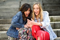 Two young women looking some awesome thing on their smart phone. Two young women looking at some awesome thing on their smart phone outdoors, sitting on urban steps. Friends girls.