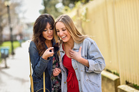 Two young women using the voice recognition of the phone outdoor. Two young women using the voice recognition of the phone. Girls sending a voice message with smart phone outdoors.