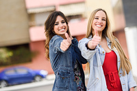 Two young women with thumbs up outdoors. Two funny female friends with thumbs up and looking at the camera in urban background.