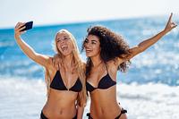 Two women taking selfie photograph with smartphone in the beach. Two young women taking selfie photograph with smart phone in swimwear on a tropical beach. Funny caucasian and arabic females wearing black bikini.
