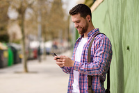 Smiling young man looking his smart phone in urban background. L. Smiling young man looking his smart phone in urban background. Guy wearing casual clothes. Lifestyle concept.