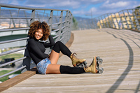 Afro hairstyle woman on roller skates sitting on urban bridge. Black woman, afro hairstyle, on roller skates sitting outdoors on urban bridge. Smiling young female with beautiful clouds at the background.