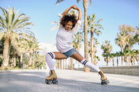 Smiling black woman on roller skates riding outdoors on beach promenade with palm trees. Smiling girl with afro hairstyle rollerblading on sunny day.. Black woman on roller skates rollerblading in beach promenade wi